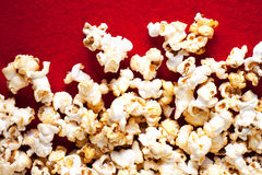 Popcorn popcorn on red textured background close up macro.  Royalty Free Stock Image