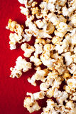Popcorn popcorn on red textured background close up macro. ю Royalty Free Stock Image