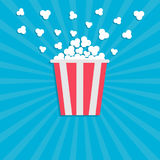 Popcorn popping. Cinema movie icon in flat design style. Red yellow strip box. Blue star burst wave background Stock Images