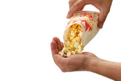 Popcorn Poured into a Hand. A man pours some popcorn into the palm of his hand on white stock photography