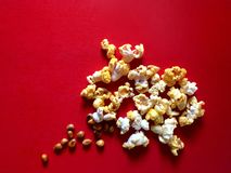 Popcorn and raw seed with cheese and butter flavor on red background. royalty free stock images
