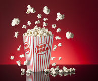 Popcorn Red Background. A box of movie popcorn flying out with a red background with copy space Royalty Free Stock Photography