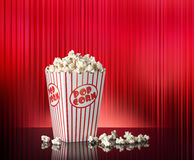 Popcorn Red Movie Background. A box of movie popcorn flying out with a red curtain theater background with room for copy space Royalty Free Stock Image