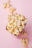 Popcorn in red and white cardboard box on the pink background. Stock Photography