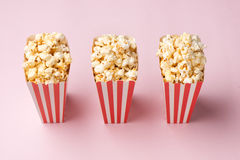 Popcorn in red and white cardboard box on the pink background. Royalty Free Stock Photography
