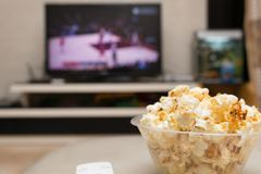 Popcorn and remote control on sofa with a TV broadcasting basketball match. On background Stock Photo