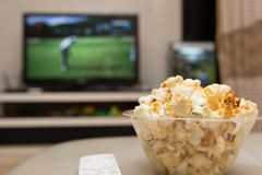 Popcorn and remote control on sofa with a TV broadcasting golf match. On background Royalty Free Stock Photos