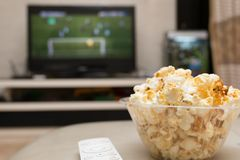 Popcorn and remote control on sofa with a TV broadcasting soccer match. On background Royalty Free Stock Image