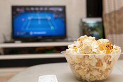 Popcorn and remote control on sofa with a TV broadcasting tennis match. On background Stock Photos