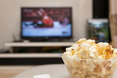 Popcorn and remote control on sofa with a TV broadcasting wrestling. On background Stock Photography