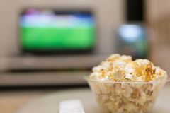 Popcorn and remote control on sofa with a TV. At background Royalty Free Stock Photography