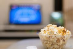 Popcorn and remote control on sofa with a TV. At background Stock Images