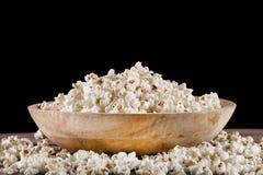 Popcorn in retro houten kom en gemorst op houten bureau royalty-vrije stock foto