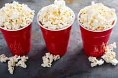 Popcorn in rode koppen Stock Afbeelding