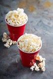 Popcorn in rode koppen Stock Afbeeldingen