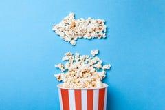 Popcorn rovesciato sotto forma di freccia a sinistra e secchio di carta nella striscia rossa sul blu Fotografie Stock Libere da Diritti