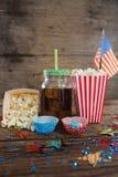 Popcorn, söt mat och den kalla drinken dekorerade med 4th det juli temat Royaltyfria Foton