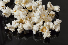 Popcorn. Salted popcorn scattered on a black table Stock Photography