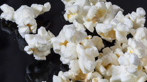 Popcorn. Salted popcorn scattered on a black table Stock Photos