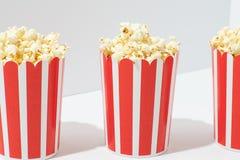 Popcorn in secchi a strisce di carta riciclabili sopra fondo bianco immagine stock