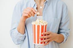 Popcorn in secchio a strisce di carta riciclabile tenuto dalla donna sopra fondo bianco immagine stock