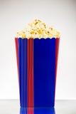 Popcorn in secchio a strisce su fondo bianco Immagini Stock Libere da Diritti