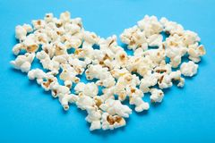 Popcorn in the shape of heart on a blue background.  royalty free stock photos