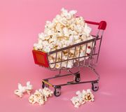 Popcorn in a shopping trolley. A bunch of popcorn on a pink background. Surrealistic concept Stock Photography