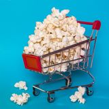 Popcorn in a shopping trolley. A bunch of popcorn on a blue background. Surrealistic concept Stock Image