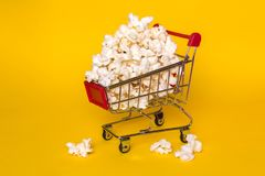 Popcorn in a shopping trolley. A bunch of popcorn on a white background. Surrealistic concept. Popcorn in a shopping trolley. A bunch of popcorn on a white Stock Images