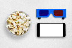 Popcorn, smartphone and 3d anaglyph glasses on table Royalty Free Stock Images