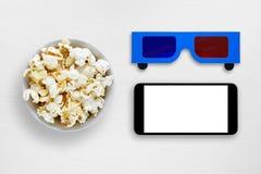 Popcorn, smartphone en 3d anaglyph glazen op lijst Royalty-vrije Stock Afbeeldingen