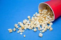 Popcorn smulade från en ask av rött royaltyfria bilder