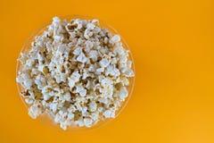 Popcorn som besk?das fr?n ovann?mnt p? gul bakgrund N?rbild Top besk?dar arkivbild