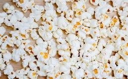 Popcorn som ordnas på träbakgrund arkivbild