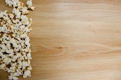 Popcorn som ordnas på träbakgrund arkivbilder