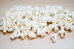 Popcorn som ordnas på träbakgrund royaltyfria bilder