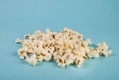 Popcorn som spills på blå bakgrund royaltyfri foto