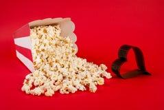 Popcorn som spills på blå bakgrund, och filmen i hjärta bildar arkivbild