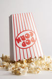 Popcorn Spill. Popcorn in a red and white striped popcorn box spilled over Royalty Free Stock Photo