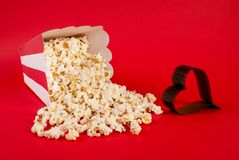 Popcorn spilled on blue background and film in heart form stock photography