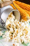 Popcorn spilled from can next to corncobs Stock Photography
