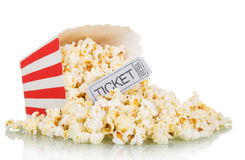 Popcorn spilled from a square box and gray movie ticket isolated on white Stock Photos
