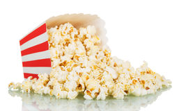 Popcorn spilled from a striped box isolated on white Royalty Free Stock Images