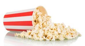 Popcorn spriddes från den stora randiga asken som isolerades på vit royaltyfri fotografi