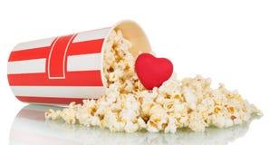 Popcorn spriddes ut boxas och röd hjärta på vit arkivfoton