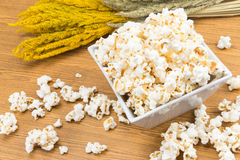 Popcorn in a square shape bowl with crop, rye beside Stock Image
