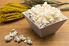 Popcorn in a square shape bowl with crop, rye beside Royalty Free Stock Photography