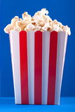 Popcorn in striped box on a blue background Stock Image