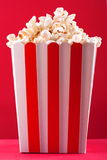 Popcorn in striped box on a red background Stock Photography